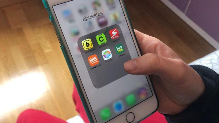 Un adolescente eligiendo una aplicación de apuestas online para apostar y que le puede general problemas de ludopatía
