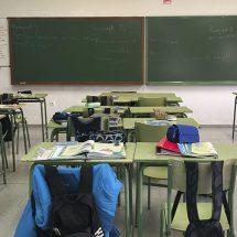 Mesas de un colegio con mochilas en los asientos y una pizarra al final.