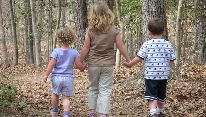 Madre pasea junto a sus hijos