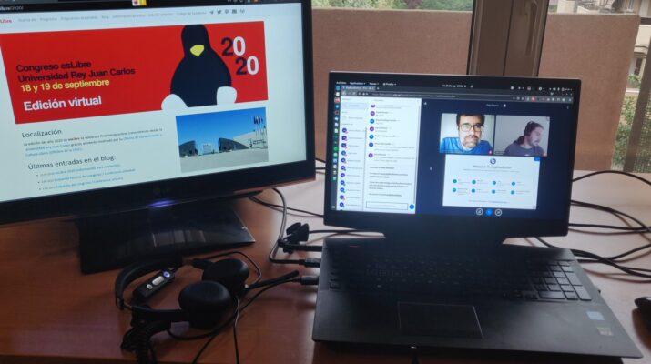 Ordenadores portátiles, uno con la página web de esLibre en la pantalla y el otro con las caras de dos hombres que van a exponer en la plataforma BigBlueButton. Se trata de la edición del congreso esLibre 2020.
