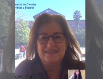 María Luisa Jalón, Decana de la Factultad de Ciencias Sociales y Jurídicas de la URJC, en videollamada durante la entrevista. De fondo, una imagen de facultad de la URJC en Vicálvaro.