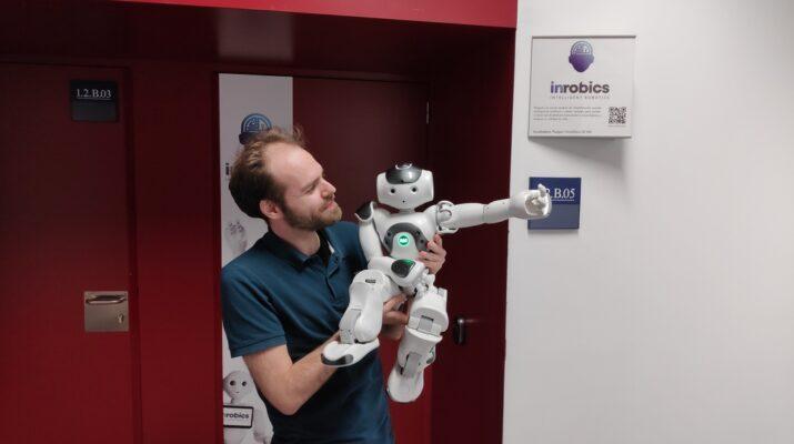 En la imagen aparece José Carlos, director técnico de Irobics, sujetando en brazos a el robot Nao. Se encuentra en la puerta de su oficina.