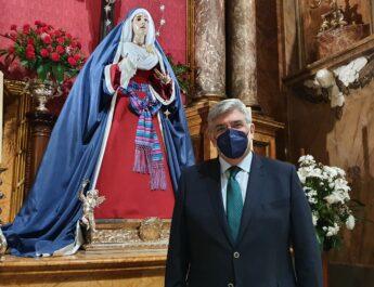 Juan Venegas, Hermano Mayor de la Hermandad de los Estudiantes de Madrid, vestido con traje y corbata. Dentro de la Basílica Pontificia de San Miguel junto a la imagen de la Virgen.