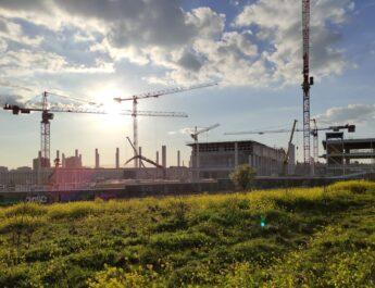 Edificio en construcción de la nueva Fábrica de Moneda y Timbre situada en Vicálvaro, rodeada de grúas y de un extenso prado verde.
