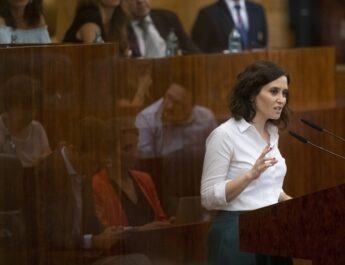 Presidenta de la Comunidad de Madrid Isabel Díaz Ayuso, con camisa blanca, hablando en alto, ayudándose de un micrófono.