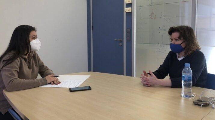 Periodista y entrevistada hablando en una sala de reuniones con distancia de seguridad y mascarillas