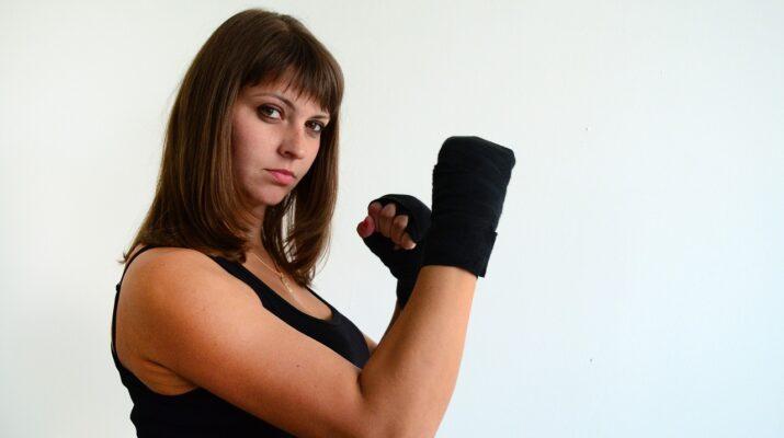 Mujer con guantes de lucha mirando desafiante a la cámara