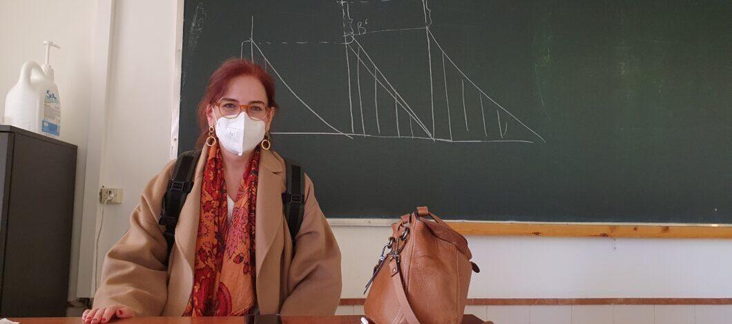 María Nieves San Emeterio posa sentada en la mesa del profesor, con mascarilla. Detrás de ella se encuentra la pizarra en la que ha dibujado gráficas.