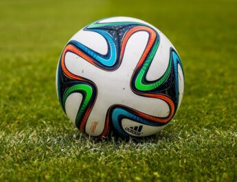 En la imagen aparece un balon de futbol en un campo de futbol. En el sueño hay cesped verde