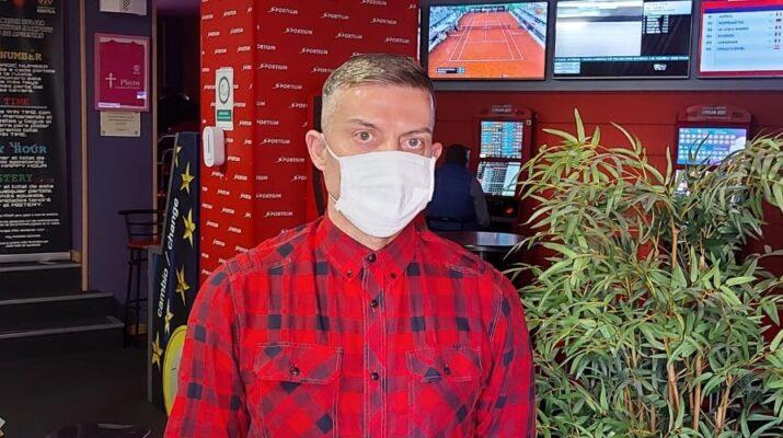 Alejandro Sánchez, propietario de seis casas de apuestas, vestido de rojo y con mascarilla mirando frente a la cámara dentro su salón de juegos en Pinto