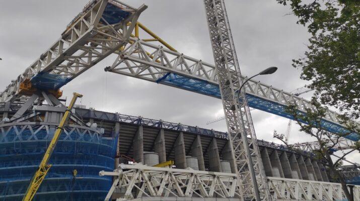 Exterior del estadio Santiago Bernabéu en el que se ven las obras: grúas, lonas para evitar desprendimientos y estructuras metálicas.