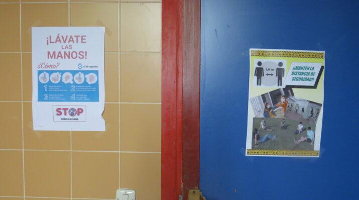 2 carteles, uno en un apuerta azul y otra en una pared de azulejo naranja que muestran medidas para no contagiar