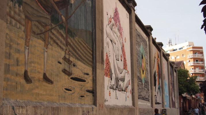 Imagen en la calle, muestra los muros de la Tabacalera situado en el barrio de Embajadores de Madrid, se pueden observar cuatro ilustraciones en los muros.