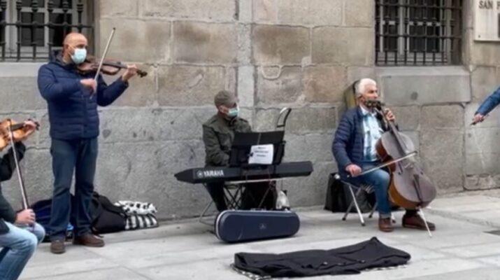 Cinco músicos callejeros tocando instrumentos como el piano y el violín a las puertas de la Academia de Bellas Artes de San Fernando
