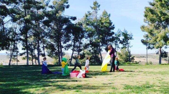Cinco niños realizando aprendizaje experimental en un prado rodeado de árboles junto a su mamá de día