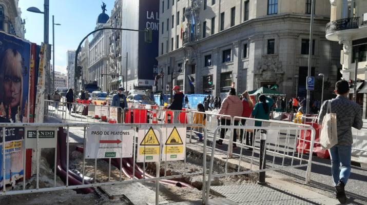 Calle Gran Vía a la altura de la calle Montera. Se ven las vallas de las obras y personas caminando entre ellas. De día.