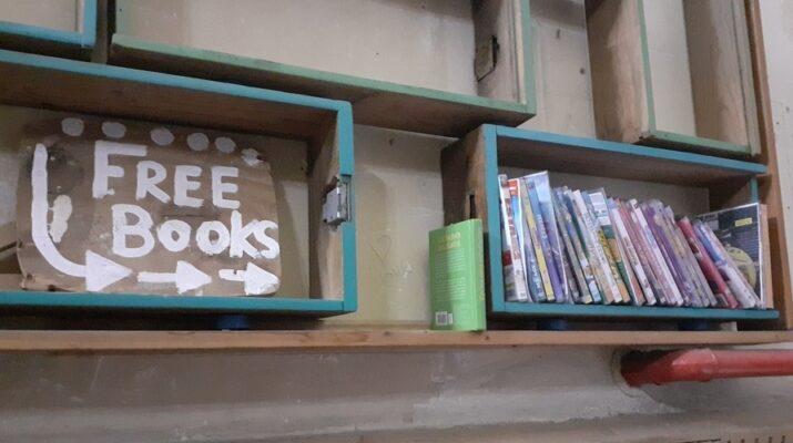 """Cartel de """"free book"""" que señala a una estantería con libros"""