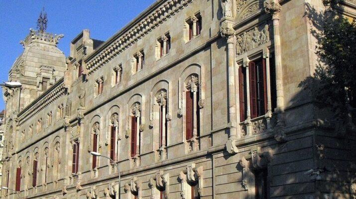 Plano lateral de la fachada del palacio de justicia de Barcelona de día. El Palacio de Justicia ocupa la parte derecha y a la izquierda el cielo.