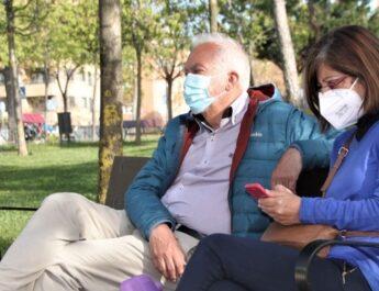 Plano medio de una pareja adulta de un hombre y una mujer sentados en el banco de un parque. Ambos llevan mascarilla.