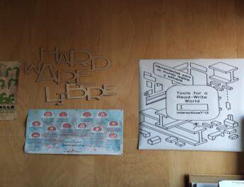 """En la imagen aparecen varios posteres en una pared del Medialab. Se puede leer: """"Hardware libre"""" y """"herramientas para un mundo legible y editable."""