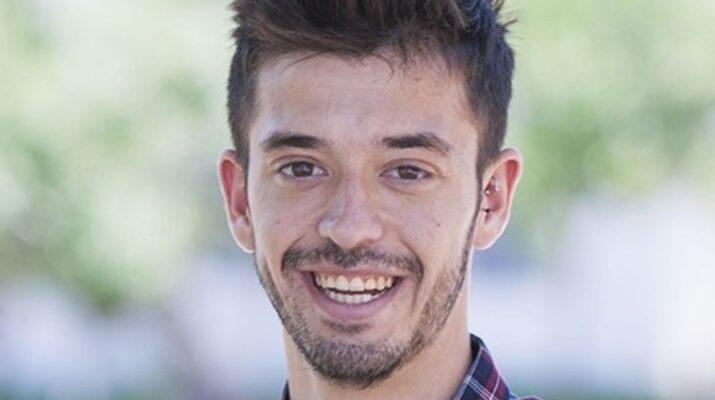 Foto de cara de Alejandro Carbonel sonriente sobre un fondo difuminado