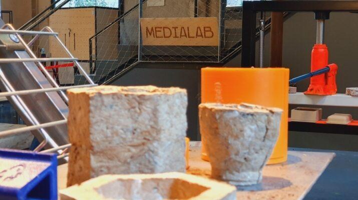 Una serie de recipientes elaborados con materiales reciclados y de fondo un cartel de Medialab