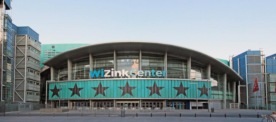 Fachada oeste del Palacio de Deportes de la Comunidad de Madrid, el Wizink Center, donde puede verse la entrada con el nombre del estadio y las estrellas características de la Comunidad de Madrid sobre un fondo azul.