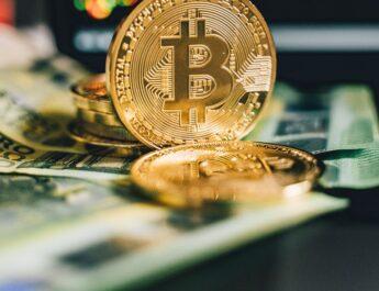 Monedas bitcoin en forma de euro, apoyadas sobre unos billetes de 100 euros.