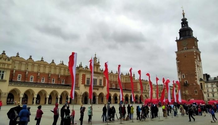 Cola para la vacunación de la COVID-19 en la Plaza del Mercado de Cracovia con el edificio del mercado de fondo y banderas de Polonia decorando la plaza.