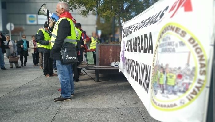 Pensionista ataviado con un pañuelo rojo y un chaleco amarillo sujeta un megáfono delante de una pancarta en defensa de unas pensiones dignas ya.