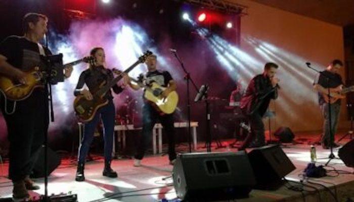 Grupo actuando sobre un escenario con set de luces