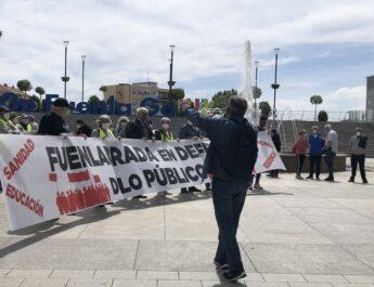 """Pensionistas de Fuenlabrada, vistiendo chalecos amarillos, sujetan una pancarta en la que se lee: """"Fuenlabrada en defensa de lo público"""". Un hombre con un megáfono corea cánticos delante de ellos."""