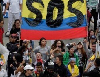 Plano picado y frontal de un grupo de unas veinte personas colombianas manifestándose con una gran bandera de Colombia en la que aparece escrito en letras mayúsculas SOS.