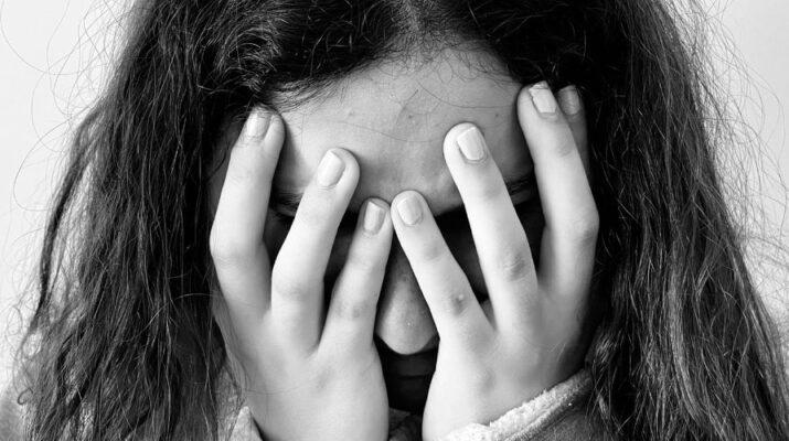 Rostro de una mujer en primer plano que, con las manos, se tapa la cara totalmente. Imagen en blanco y negro.
