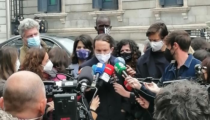 Pablo Iglesias declarando a la prensa, rodeado de micrófonos a las afueras del Congreso de los Diputados