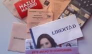 Varios sobres y papeletas de las elecciones de Madrid en 2021. Aparecen esparcidos por una mesa con luz de día.