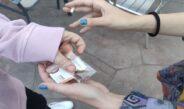 En la imagen aparecen las manos de dos personas en un negocio de compraventa de droga propia del mercado negro. Una de las manos sostiene un billete de 10 euros y una bolsita de droga. La otra mano está cogiendo uno de los dos elementos.