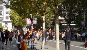 Personas caminando hacía la manifestación de Vox en los alrededores de la Plaza de Colón. En la parte superior se ven las hojas de los árboles, las personas que caminan llevan banderas de España.
