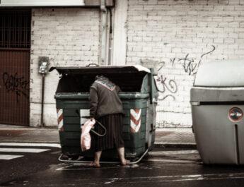 Una mujer buscando en un contenedor de basura.