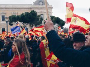 Imagen de banderas de España y una de la Unión Europea elevadas por las personas en una manifestación de Vox.