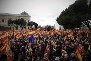 Multitud de personas desde un ángulo alto, levantando banderas de España y una de la Unión Europea en una manifestación de Vox.