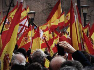 Imagen de banderas de España elevadas por las personas en una manifestación, en la parte inferior se recortan las cabezas de las personas que aguantan las banderas.