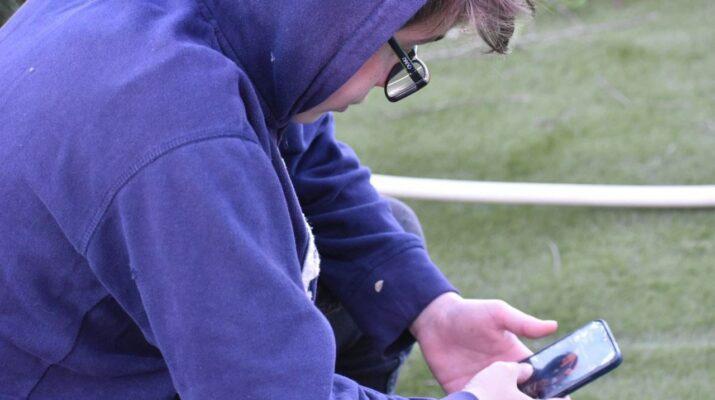 Un adolescente mirando las redes sociales en su móvil