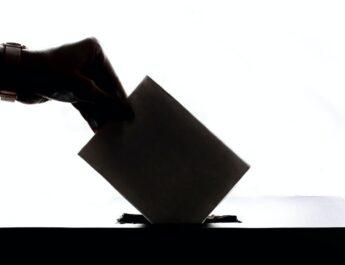 Foto en blanco y negro. Una mano introduce el sobre de su voto en una urna electoral.